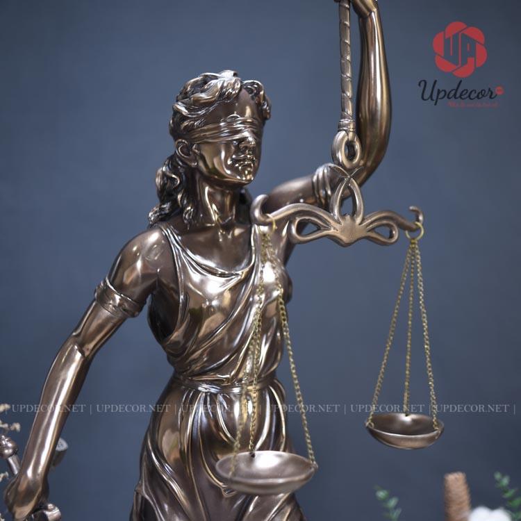 Tay trái của nữ thần cầm cán cân tượng trưng cho sự công bằng của luật pháp