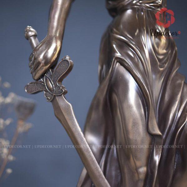 Tay phải của nữ thần cầm một thanh gươm thể hiện cho quyền uy của pháp luật