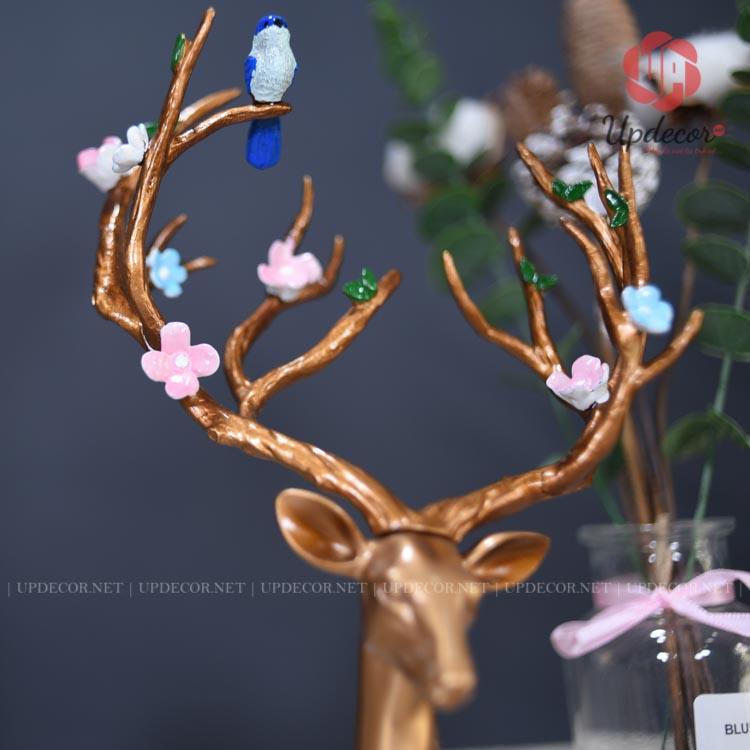 Hình ảnh chú chim đậu trên bộ sừng được trang trí hoa mai nở gợi cho chúng ta về khoản khắc của mùa xuân đang về