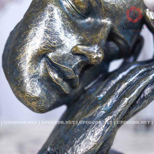 Đôi bàn tay đang e ấp trên gương mặt của bức tượng