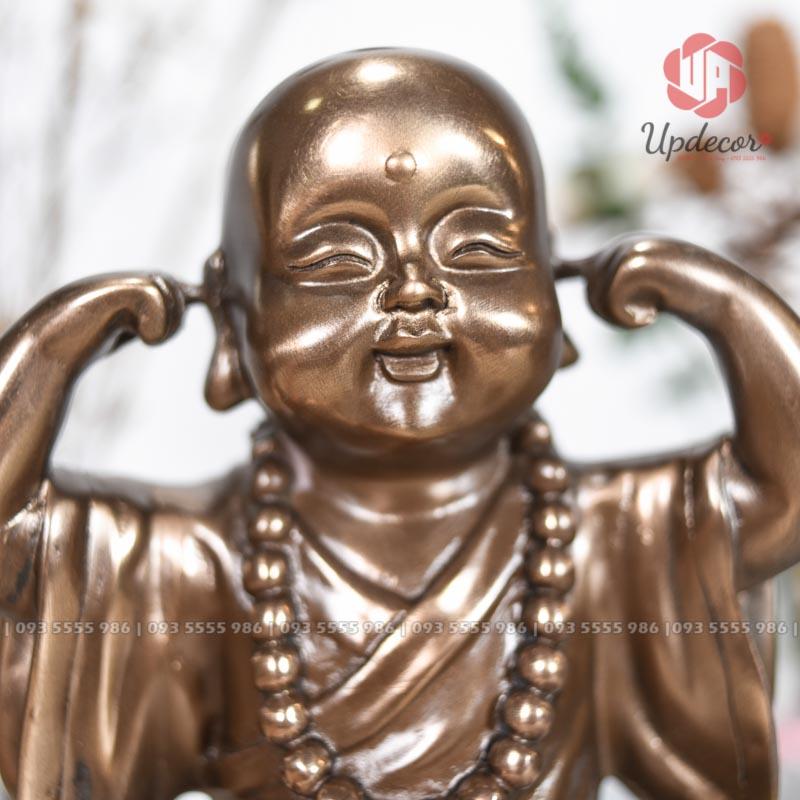 Một gương mặt rất bầu bĩnh và đáng yêu của chú tiểu đang lấu hai ngón tay bịt lấy lỗ tai để không phải nghe những lời đồn thổi xấu xa từ bên ngoài